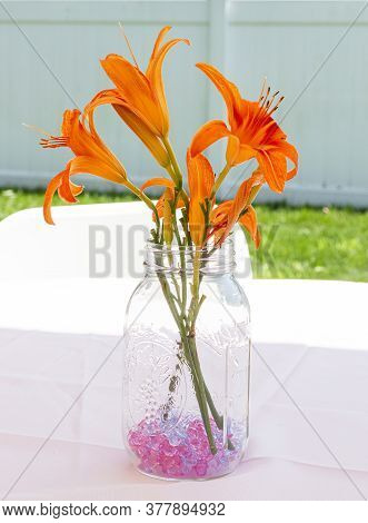 Centerpiece Of Orange Tiger Lilies In A Jar With Purple Stones On A Table In A Backyard For An Event