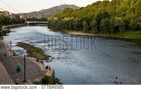 Turin, Piedmont, Italy. July 2020. Beautiful Evening View Of The Po River. People Enjoy Relaxing Alo