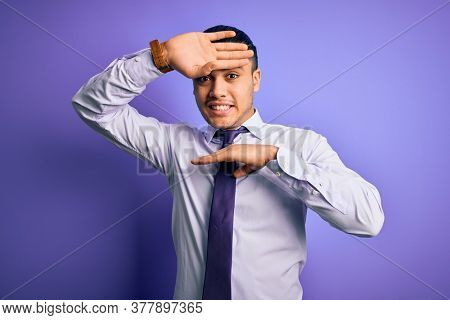 Young brazilian businessman wearing elegant tie standing over isolated purple background Smiling cheerful playing peek a boo with hands showing face. Surprised and exited