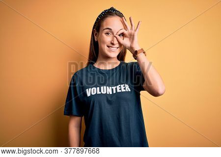 Young beautiful woman wearing volunteer t-shirt doing volunteering over yellow background doing ok gesture with hand smiling, eye looking through fingers with happy face.