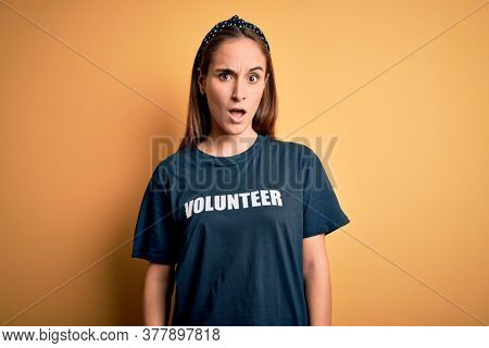 Young beautiful woman wearing volunteer t-shirt doing volunteering over yellow background In shock face, looking skeptical and sarcastic, surprised with open mouth