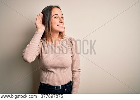 Young beautiful woman wearing casual sweater standing over isolated white background smiling with hand over ear listening an hearing to rumor or gossip. Deafness concept.