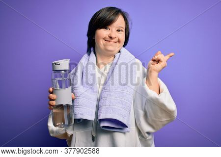 Young down syndrome fitness woman training at gym holding water bottle and sport towel very happy pointing with hand and finger to the side