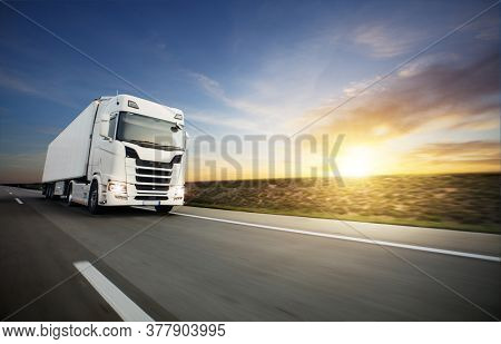 European truck on motorway with beautiful sunset sky and dramatic clouds. Transportation and cargo theme, free space for text.