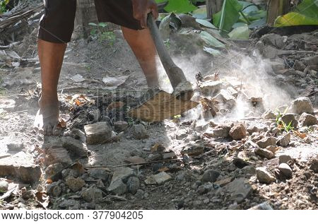 People Using A Hoe To Level The Ground And Dusty Stones In The Garden During The Day