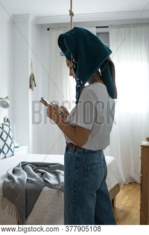 Cute Woman With A Towel On Her Head Texting With Her Cell Phone. Interior Photography, Modern Decor.