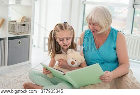 Cute granny reading book to little granddaughter holding toy sitting on floor in playroom