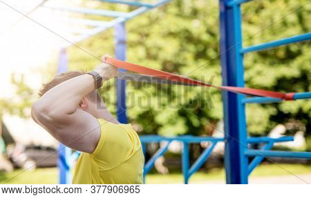 Man using resistance rubber band for fitness in sunny park