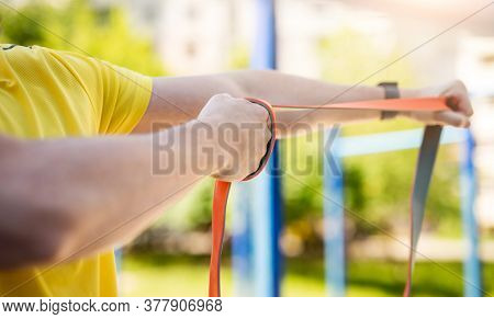 Man exercising with resistance rubber band in street, close up