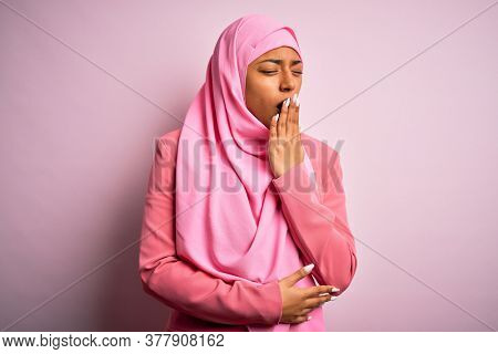 Young African American afro woman wearing muslim hijab over isolated pink background bored yawning tired covering mouth with hand. Restless and sleepiness.