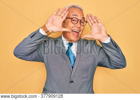 Middle age senior grey-haired handsome business man wearing glasses over yellow background Smiling cheerful playing peek a boo with hands showing face. Surprised and exited