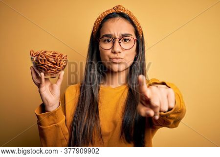 Young beautiful asian woman holding bowl with german baked pretzels over yellow background pointing with finger to the camera and to you, hand sign, positive and confident gesture from the front