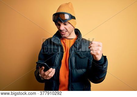 Young handsome skier man wearing ski goggles using smartphone over yellow background annoyed and frustrated shouting with anger, crazy and yelling with raised hand, anger concept