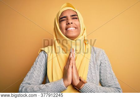 Young beautiful african american girl wearing muslim hijab over isolated yellow background begging and praying with hands together with hope expression on face very emotional and worried. Begging.