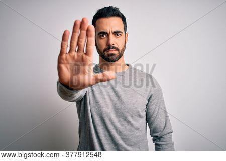 Young handsome man with beard wearing casual sweater standing over white background doing stop sing with palm of the hand. Warning expression with negative and serious gesture on the face.