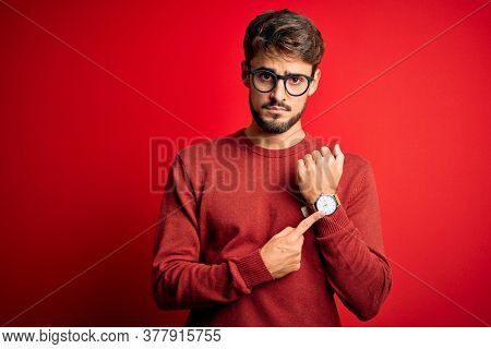 Young handsome man with beard wearing glasses and sweater standing over red background In hurry pointing to watch time, impatience, looking at the camera with relaxed expression
