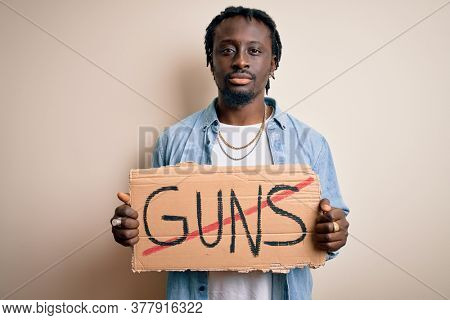 Young african american man asking for peace holding banner with prohibited guns message with a confident expression on smart face thinking serious