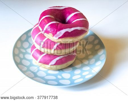 Three Pink And White Doughnuts On Colorful Plate On White Background Close-up. Junk Food. Sweet Food