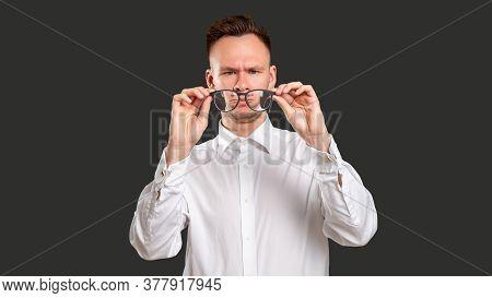Nerd Lifestyle. Eyewear Style. Skeptic Man Trying Wearing Eyeglasses Isolated On Black. Vision Corre