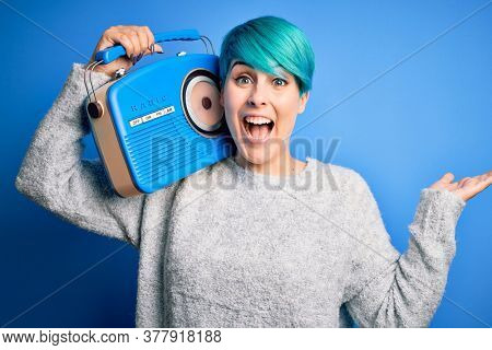Young woman with blue fashion hair listening to music holding vintage portable radio very happy and excited, winner expression celebrating victory screaming with big smile and raised hands