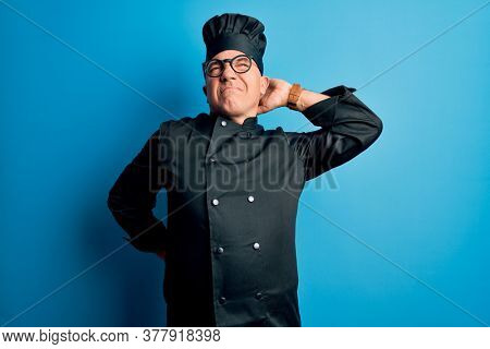 Middle age handsome grey-haired chef man wearing cooker uniform and hat Suffering of neck ache injury, touching neck with hand, muscular pain