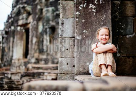 Little girl in beautiful ancient Bayon temple in Siem Reap Cambodia