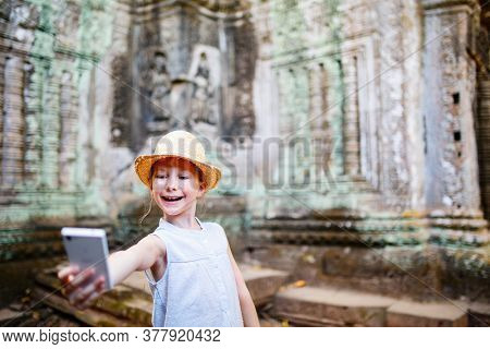 Little girl in ancient Angkor Wat temple in Siem Reap, Cambodia