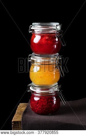 Strawberry, Orange And Raspberry Jams In Glass Jars Against The Black Background. Three Jars Of Jam