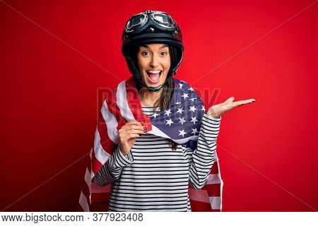 Young beautiful patriotic motorcyclist woman wearing moto helmet and united states flag very happy and excited, winner expression celebrating victory screaming with big smile and raised hands