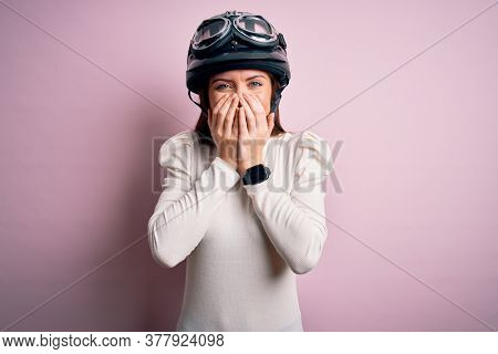 Young beautiful motorcyclist woman with blue eyes wearing moto helmet over pink background laughing and embarrassed giggle covering mouth with hands, gossip and scandal concept