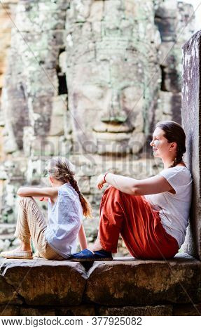 Family visiting ancient Bayon temple in Angkor Archeological area in Cambodia