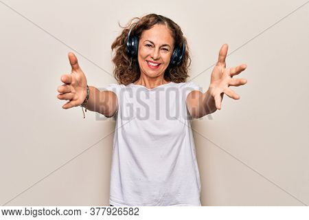 Middle age beautiful woman listening to music using headphones over white background looking at the camera smiling with open arms for hug. Cheerful expression embracing happiness.