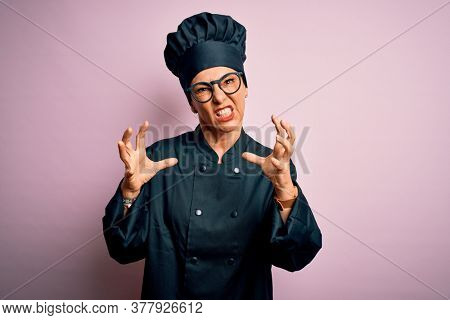 Middle age brunette chef woman wearing cooker uniform and hat over isolated pink background Shouting frustrated with rage, hands trying to strangle, yelling mad