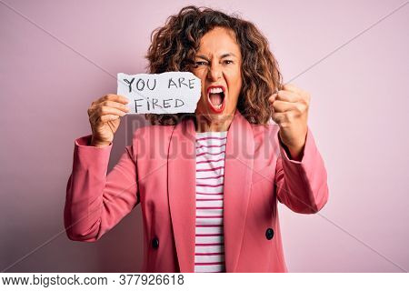 Middle age woman holding paper with you are fired message over isolated pink background annoyed and frustrated shouting with anger, crazy and yelling with raised hand, anger concept