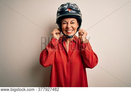 Middle age motorcyclist woman wearing motorcycle helmet over isolated white background covering ears with fingers with annoyed expression for the noise of loud music. Deaf concept.