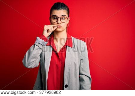Young beautiful brunette businesswoman wearing jacket and glasses over red background mouth and lips shut as zip with fingers. Secret and silent, taboo talking