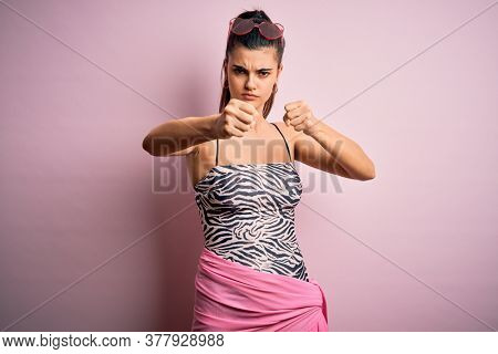 Young beautiful brunette woman on vacation wearing swimsuit over pink background Punching fist to fight, aggressive and angry attack, threat and violence