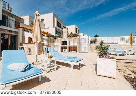 White Wooden Deckchairs In The Villa, Near The Sea Shore. Blue Soft Pillow. The Courtyard Of The Vil