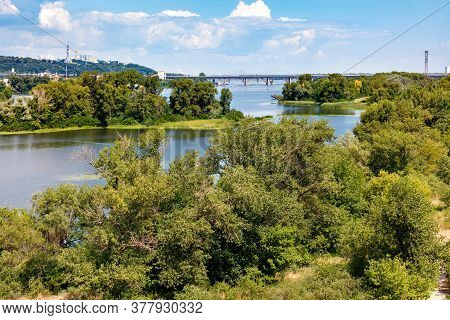 The Picturesque Islands On The Dnipro River Are Overgrown With Trees And Green Grass. View Of The Br