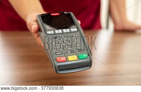 Cashier Offering Pos Terminal For Payment With Credit Card.