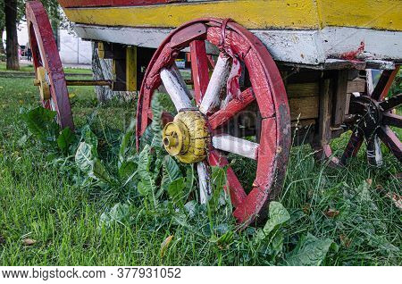 Red Wooden Wheel Of An Old Cart In Green Grass. Obsolete Vehicles. Old Cart As An Element Of Landsca
