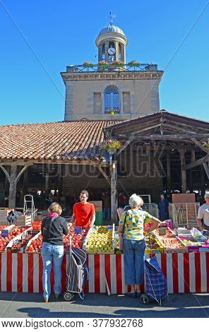 Revel, Languedoc - Roussillon, France - September 14, 2013: Shopper Buying Fruit At The Hisotric Cov