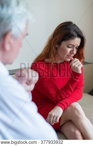 Desperate Woman At A Psychotherapy Session. Male Psychotherapist Talking To A Female Patient With De