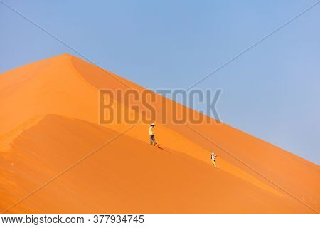 Kids brother and sister climbing up famous red sand dune Big Daddy  in Sossusvlei Namibia