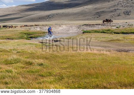 A Motorcyclist Tries To Drive Along A Road Filled With Water During A Flood After Rain. Horses On Th
