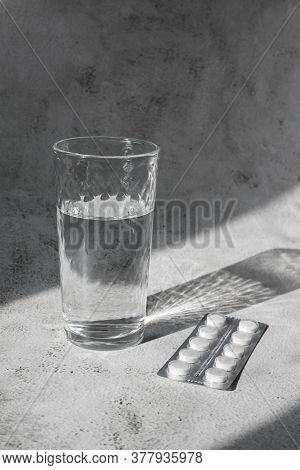 Transparent Glass Of Water With White Pills In Contrast Light. Headache Or Hangover Concept