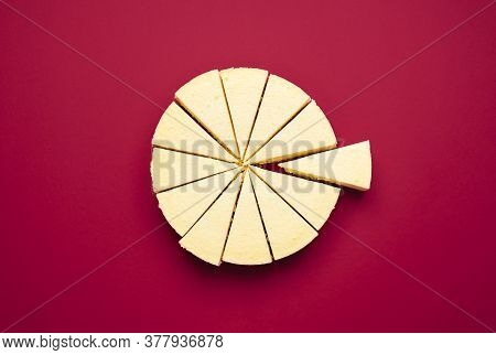 Sliced Cheesecake In Equal Pieces Isolated On A Red Background. Top View Of Creamy Cheesecake Cut In