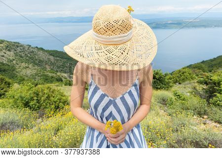 Young Woman Wearing Striped Summer Dress And Straw Hat Standing In Super Bloom Of Wildflowers, Holdi