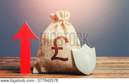 British Pound Sterling Money Bag With A Shield And A Red Arrow Up. Increasing The Maximum Amount Of