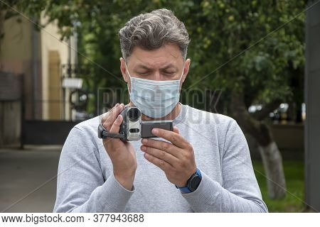 Street Portrait Of A Man In A Medical Mask Who Takes Video On A Hidden Video Camera. Concept: Survei